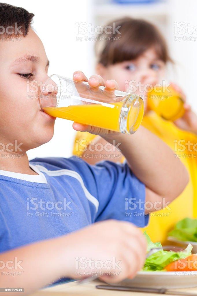 Children drinking orange juice royalty-free stock photo