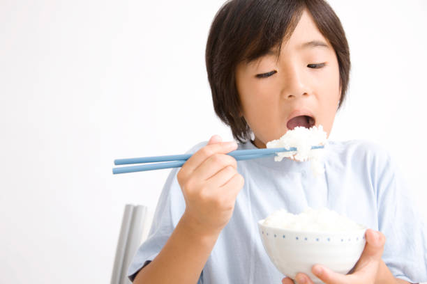 Children eat rice Children eat rice ASAP stock pictures, royalty-free photos & images