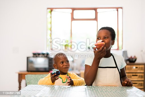 Happy children eating cupcakes in the kitchen with polka dot table cloth