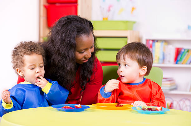 Children eating fruit at a nursery with their carer stock photo