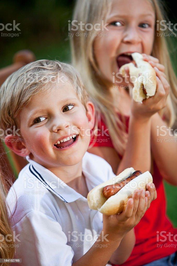 Children eating hotdogs royalty-free stock photo