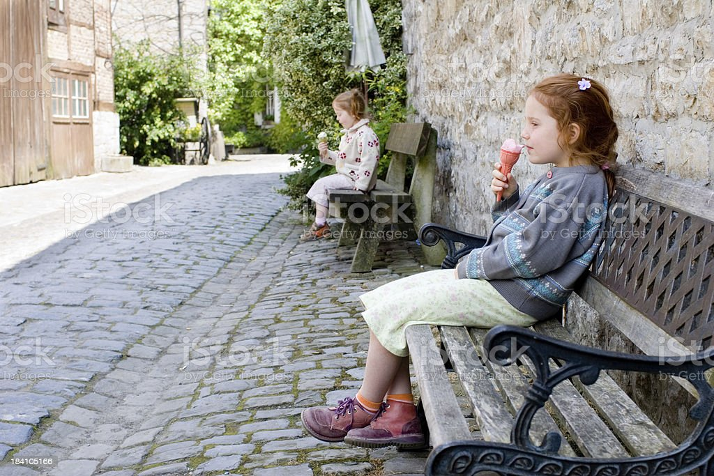 "Children eating icecream in medieval village ""Two little girls, aged 3 and 5 years, sitting each on a separate bench, eating ice cream. Background is a little medieval village.Location: Durbuy, Belgium."" Arguing Stock Photo"