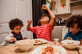 A family around a table eating spaghetti one child dangles spaghetti into his mouth