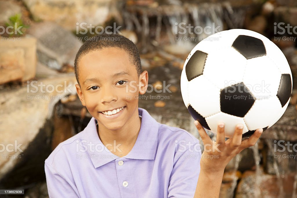 Children: Elementary age boy holding soccer ball by waterfall royalty-free stock photo