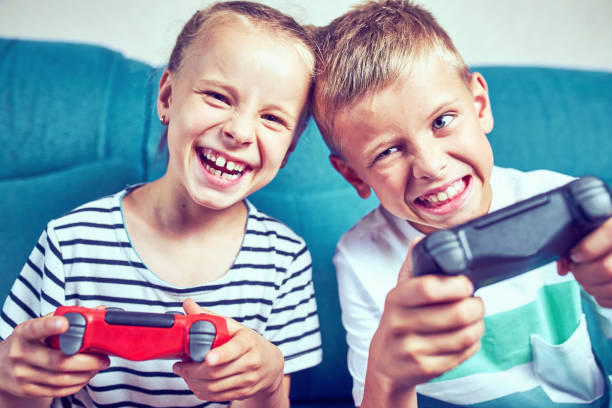 Children emotionally play a video game while sitting on the couch. stock photo