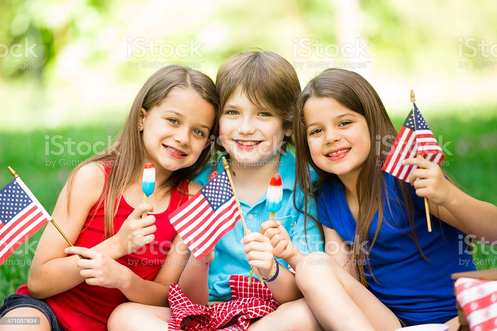 Children enjoy July 4th picnic in summer. American flags, popsicles. stock photo