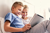 Growing up with technology. Two little smiling kids sitting on bed at home and playing games on their technology tablet