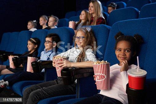 istock Children enjoying film premiere in movie theatre. 1147577625