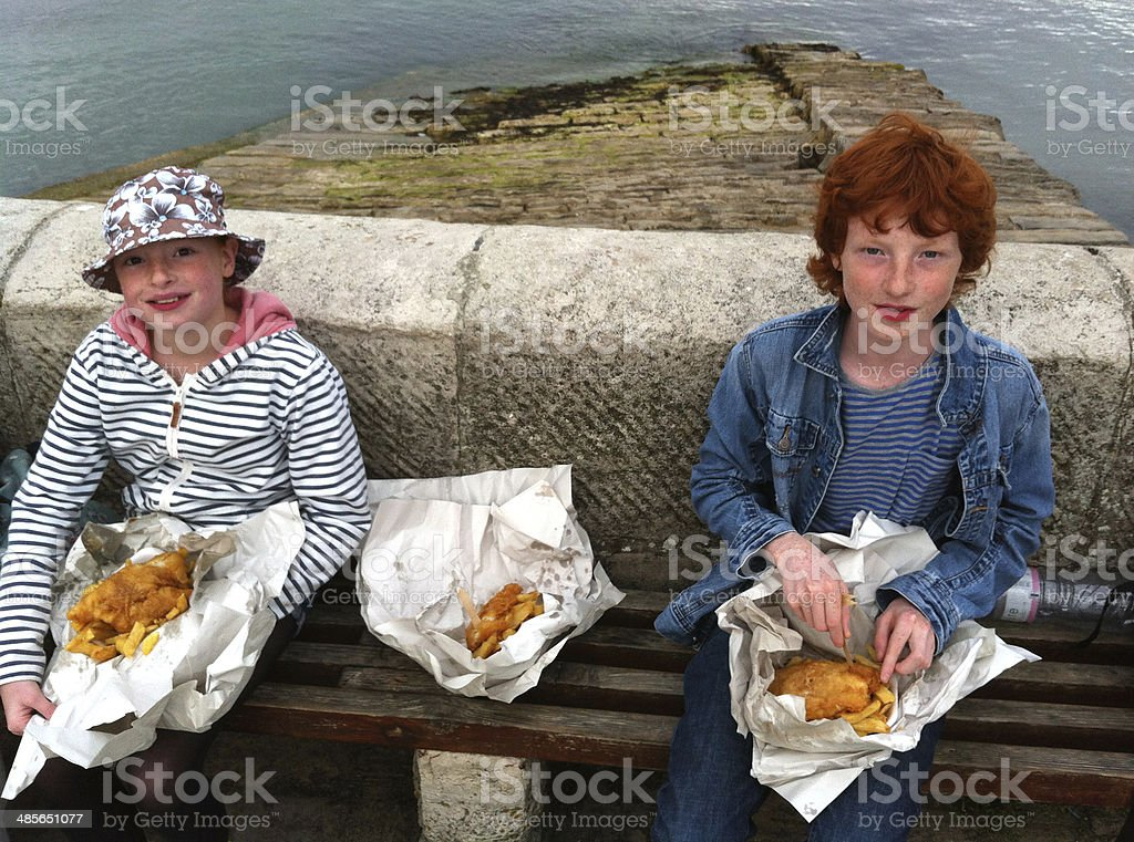 Children enjoying fish and chips out of paper at harbour stock photo