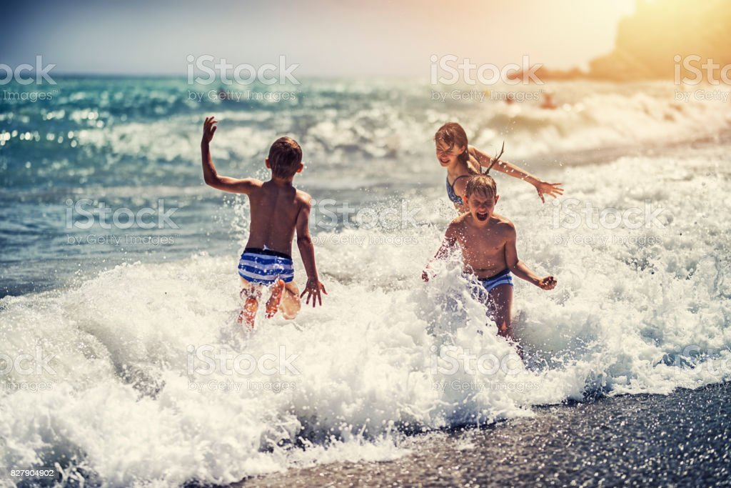 Children enjoying huge waves on beach stock photo
