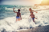 Brothers and sister are having splshing fun on beach in big waves. Andalusia, Costa del Sol, Spain. Children are aged 7 and 11.\n