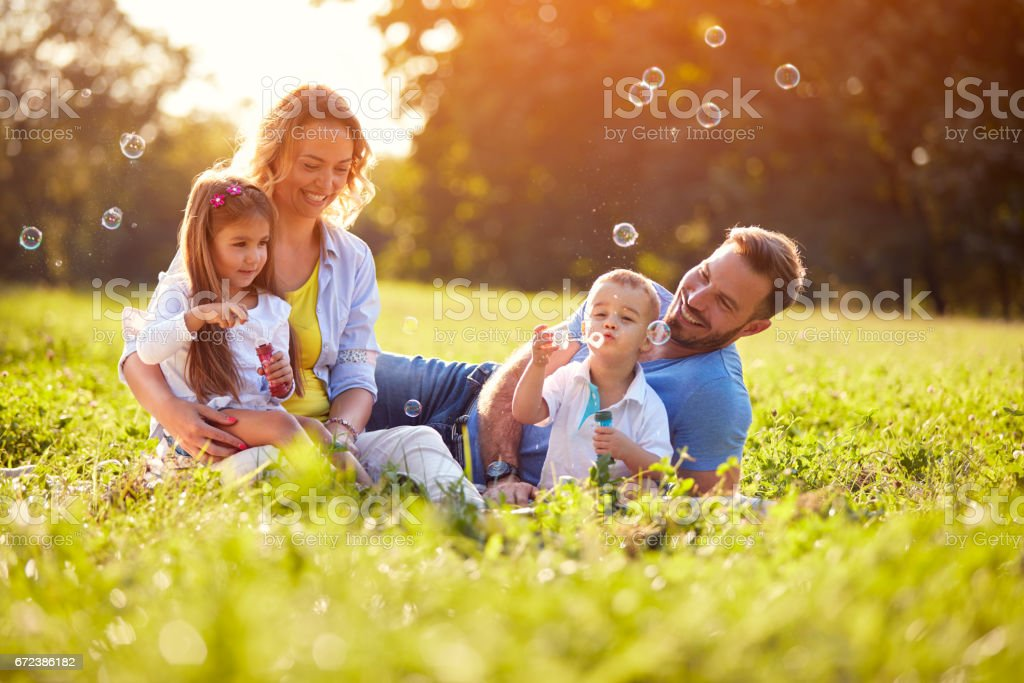 Children enjoying in making soap bubbles stock photo