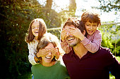 Playful children covering eyes of parents while enjoying piggyback ride in park