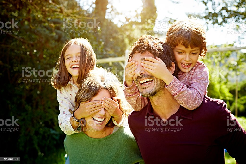 Children enjoying piggyback ride on parents stock photo