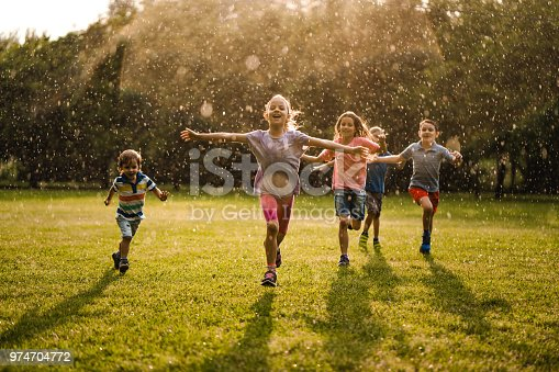 Little kids running on the rain