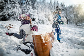 Kids hiding behind a toboggan, having a snowball fight. Brother and sister are enjoying beautiful winter day. Nikon D850