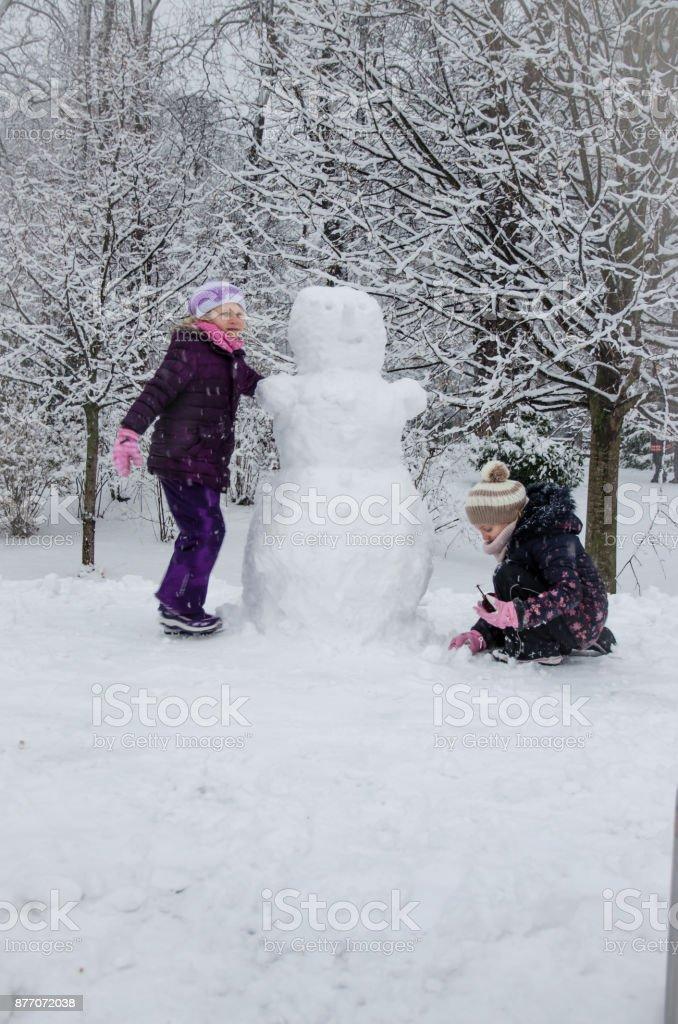 children enjoying winter atmosphere in the park stock photo