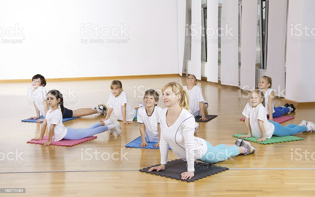 Children exercising with female trainer at the gym.