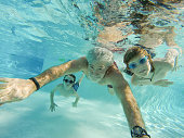 Father, Grandfather, and children swim underwater in pool in summer