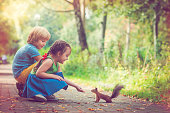 Little girl and boy feed squirrel in park in summer