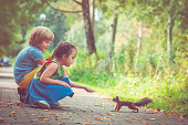 Happy little girl and boy feeding a squirrel in a summer park