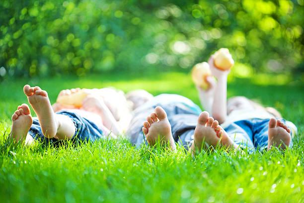 Pés de crianças na grama verde - foto de acervo