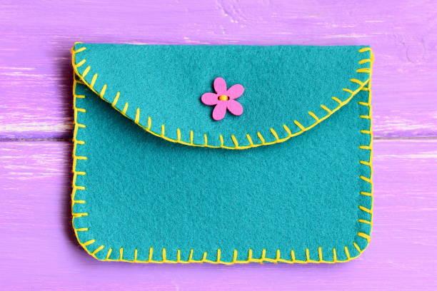 kinder filz/geldbörse auf einem hölzernen hintergrund isoliert. handtasche aus filz mit einem zierstich und verziert mit einem rosa knopf. einfaches kunsthandwerk. ansicht von oben. closeup - kinderhandtaschen stock-fotos und bilder