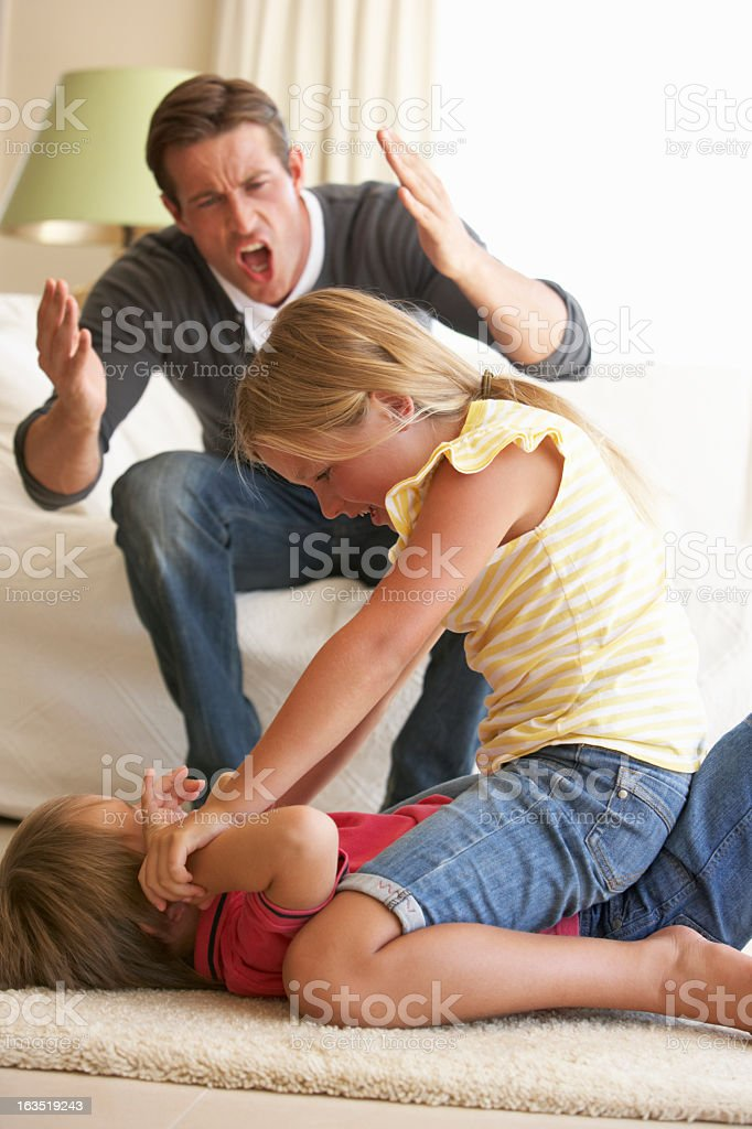 Children Fighting In Front Of Father At Home stock photo