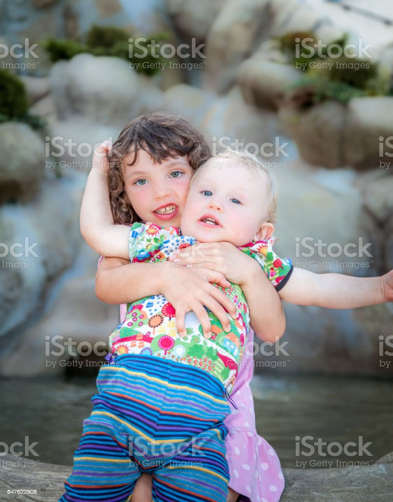 Children fooling around. Girl hugs little boy outdoors and arguing. royalty-free stock photo