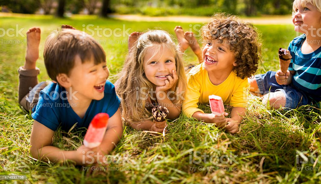 Children friends eating ice creams in park stock photo