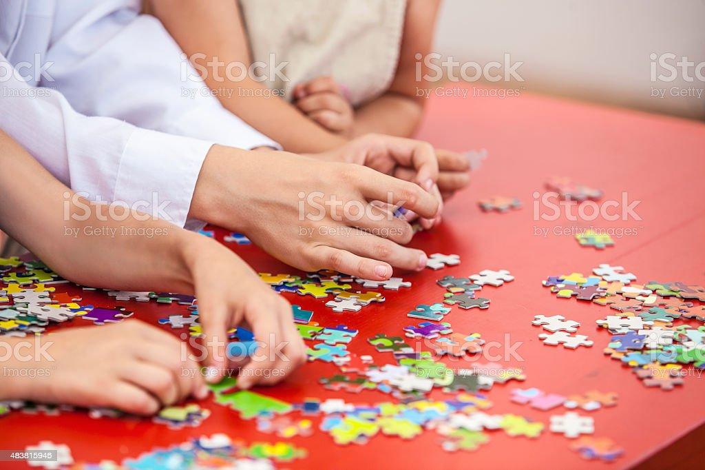 Children, friends hands assemble the puzzle stock photo