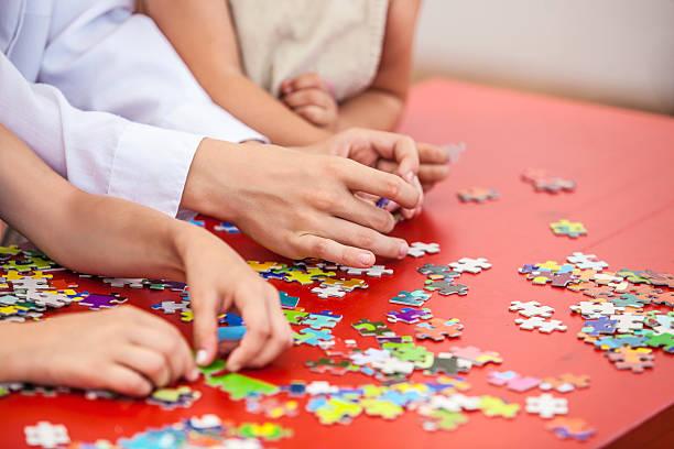 children, friends hands assemble the puzzle - s stockfoto's en -beelden