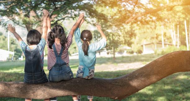 kinder freundschaft konzept mit glücklichen mädchen kinder in den park mit spaß sitzen unter baum schatten spielen zusammen genießen gutes gedächtnis und moment der student lebensstil mit freunden in der schule mal tag - sommerfest kindergarten stock-fotos und bilder