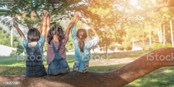 Photo of Children friendship concept with happy girl kids in the park having fun sitting under tree shade playing together enjoying good memory and moment of student lifestyle with friends in school time day