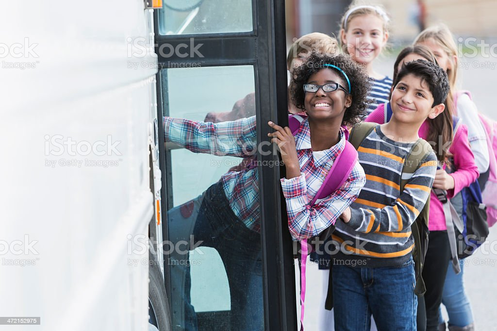 Children getting on school bus stock photo