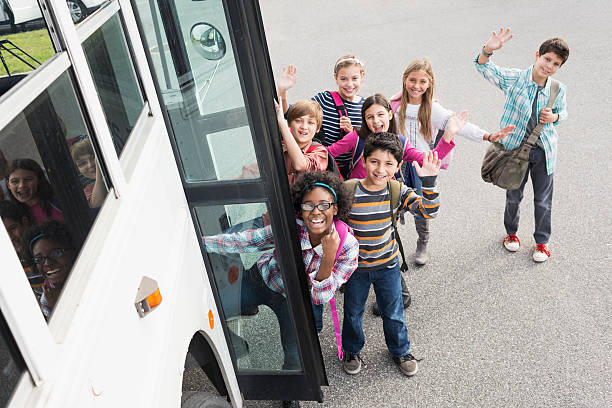 Children getting on school bus Group of multi-ethnic elementary school children (10-12 years) getting on school bus. field trip stock pictures, royalty-free photos & images