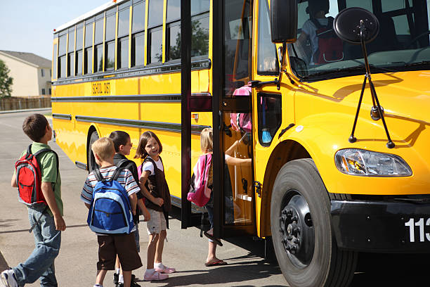 children getting on to the yellow school bus - school buses stock pictures, royalty-free photos & images