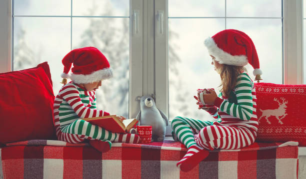children girl and boy is sad on christmas morning by the window - family christmas imagens e fotografias de stock