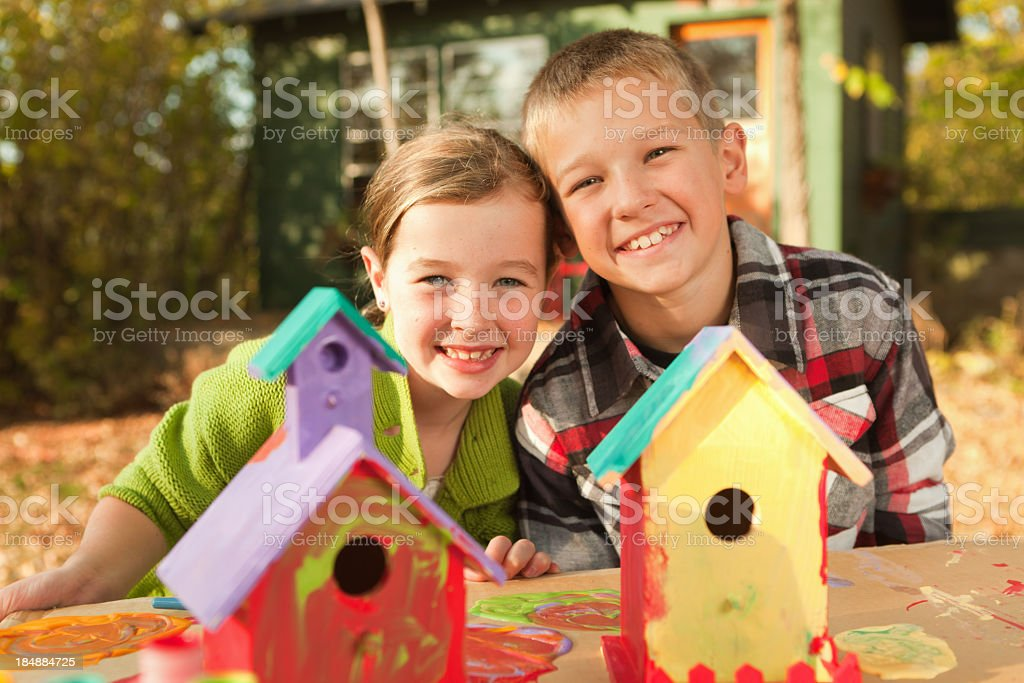 Children, Girl and Boy Painting Playful Wooden Birdhouse Craft Project royalty-free stock photo