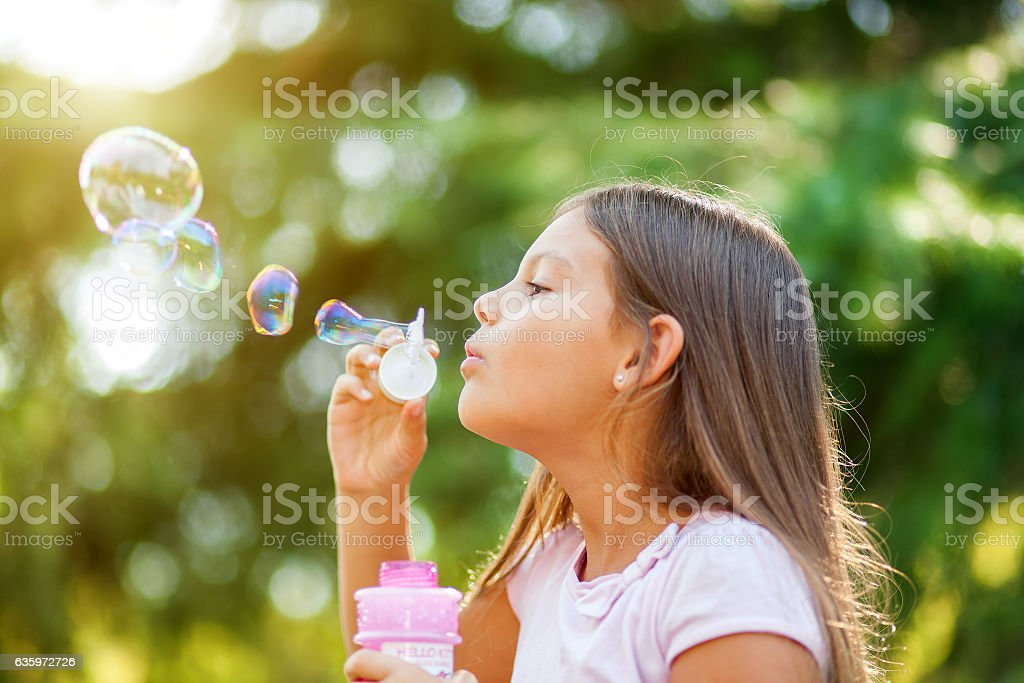 Children girl blowing soap bubbles outdoor stock photo