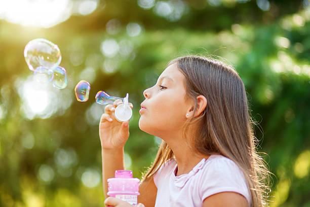 Children girl blowing soap bubbles outdoor - foto de stock