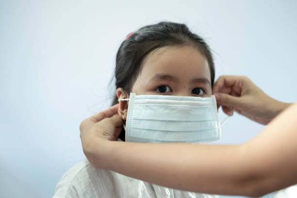 Children girl waring mask to protect Covid-19 virus and PM2.5 air pollution stock photo