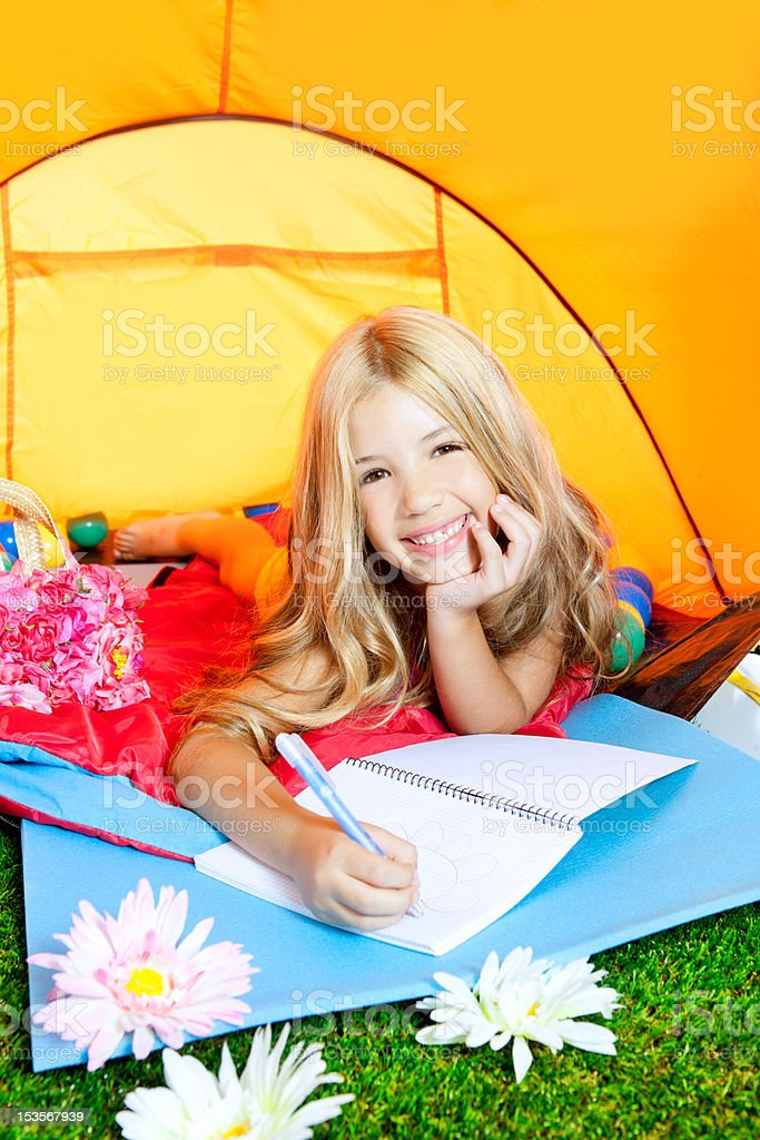 Children girl writing notebook in camping tent with flowers royalty-free stock photo