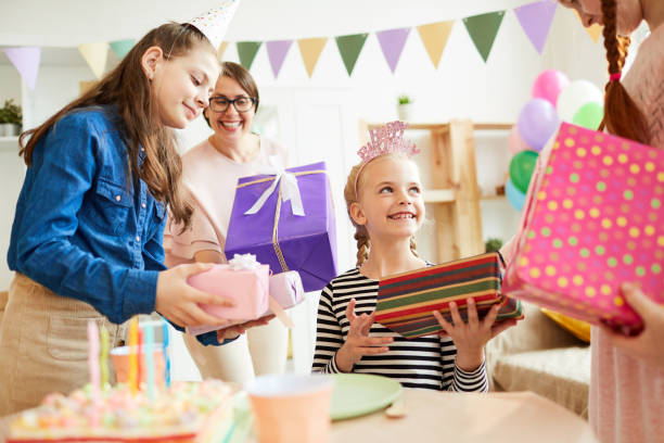 Children giving Birthday Gifts Portrait of cute girl receiving gifts surrounded by friends a during Birthday party, copy space group of friends giving gifts to the birthday girl stock pictures, royalty-free photos & images