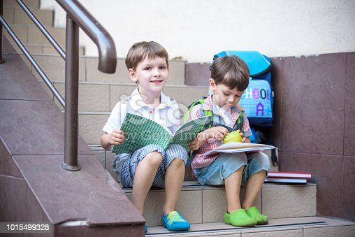 istock Children go back to school. Start of new school year after summer vacation. Two Boy friends with backpack and books on first school day 1015499328