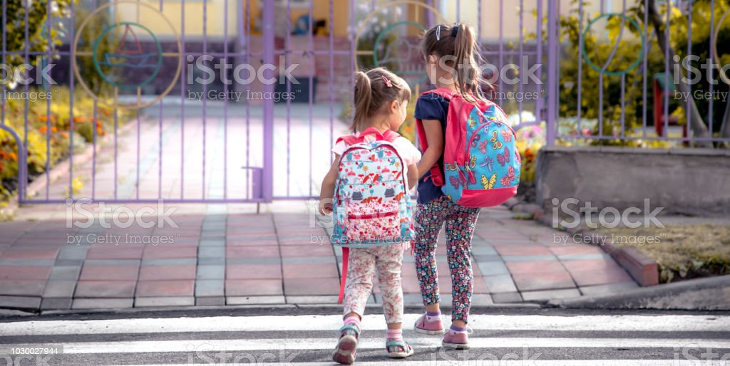 Children go to school, happy students with school backpacks and holding hands together stock photo