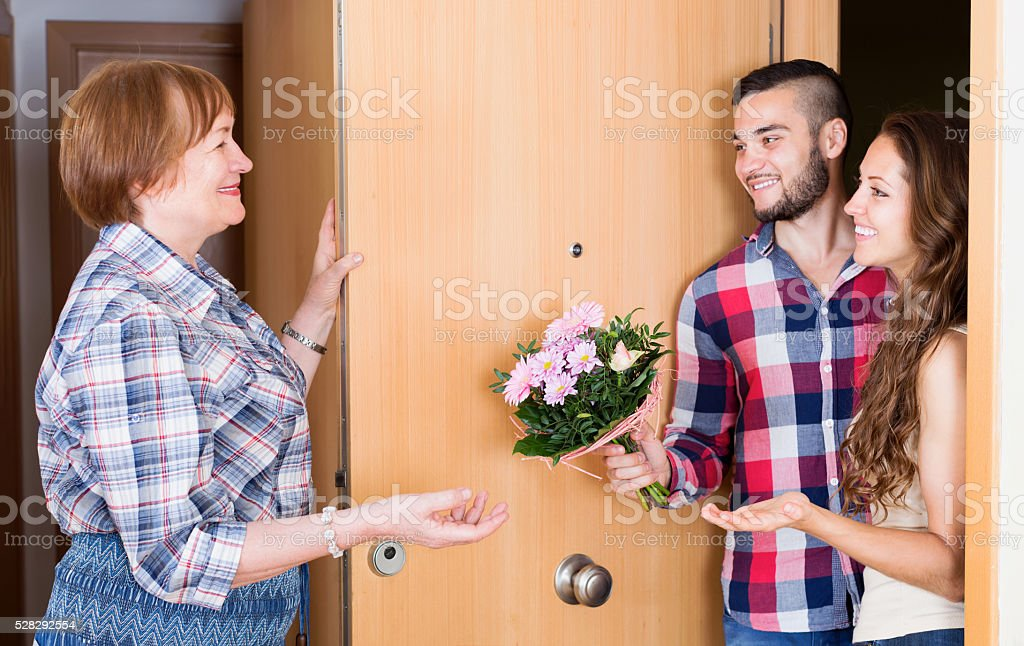 Children greeting mother  with flowers stock photo