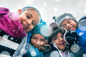 Group of kids wrapped up in warm clothes hugging outdoors in winter, low point of view.