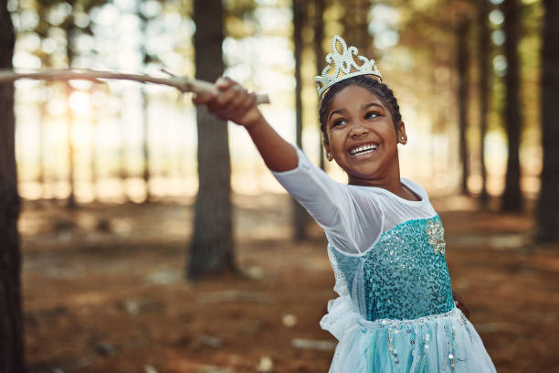 Children grow and learn with the power of their imagination Shot of a little girl dressed up as a princess and playing in the woods dressing up stock pictures, royalty-free photos & images