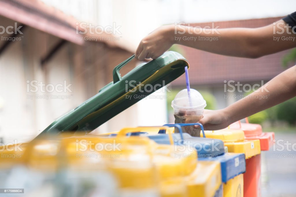 children hand throwing empty plastic bottle into the trash.saving environment by throwing plastic jung in to the recycle bin or garbage stock photo